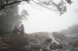 Trekkers sitting on the top of Đỗ Quyên Waterfall in a rainy day